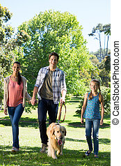 Happy family walking their dog in the park