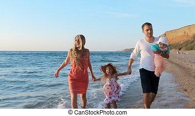 Happy family walks along the seashore