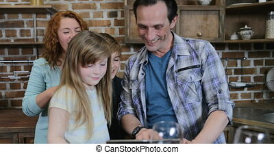 Happy Family Watch Video On Digital Tablet In Kitchen During Cooking Parents With Two Children At Home Talking