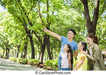 Happy family watching and showing to something in the park