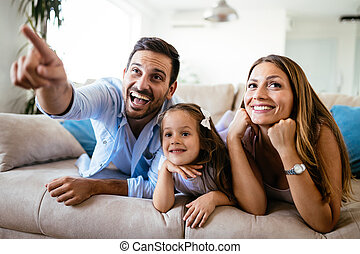 Happy family watching television at their home