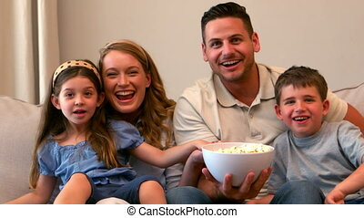Happy family watching television eating popcorn in slow motion