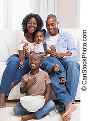 Happy family watching television to