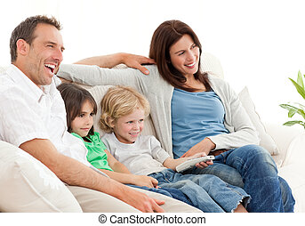 Happy family watching television together on the sofa