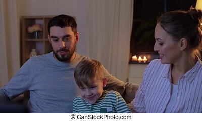 happy family watching tv at home at night