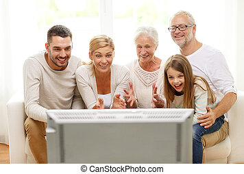 happy family watching tv at home - family, happiness,...