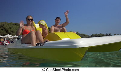 Happy family waving hands while sailing on pedal boat