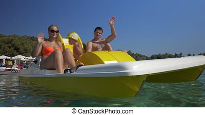 Happy family waving hands while sailing on pedal boat -...