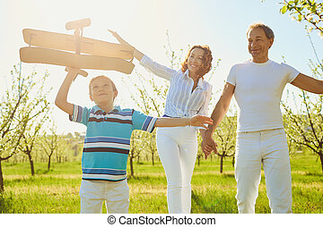 Happy family with a child outdoors in summer.