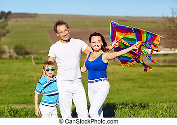 Happy family with a kite on nature in spring, summer.