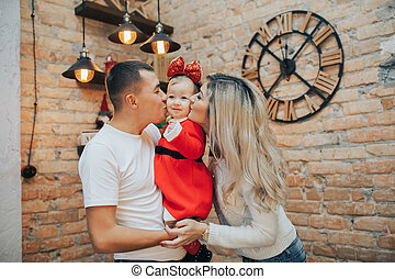 Family with a small daughter celebrating a New Year or Christmas day