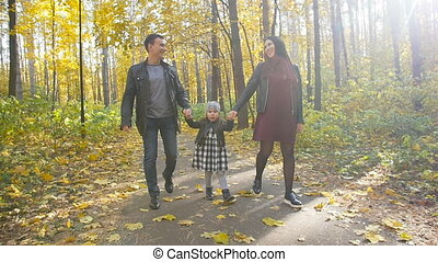 Happy Family with a small daughter walk in autumn park