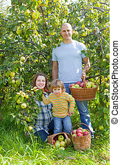 Happy family with apples in garden