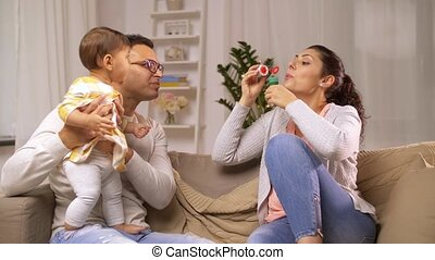 happy family with baby and soap bubbles at home - family,...
