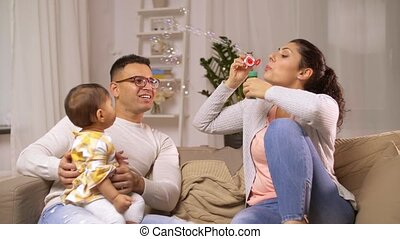 happy family with baby and soap bubbles at home