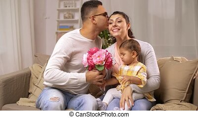 happy family with baby girl and flowers at home