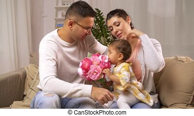 happy family with baby girl and flowers at home - family,...