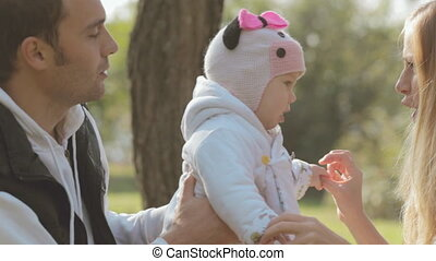 Happy family with baby on nature in autumn park