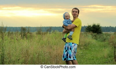 Happy family with baby playing in the field. Beautiful orange sky before sunset. Smiles and joy