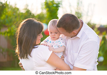 Happy family with baby son in park