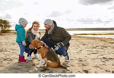 happy family with beagle dog on beach