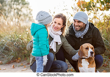 happy family with beagle dog outdoors in autumn