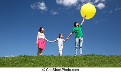 Happy family with bubble on hill