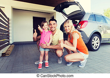 happy family with car showing thumbs up at parking -...