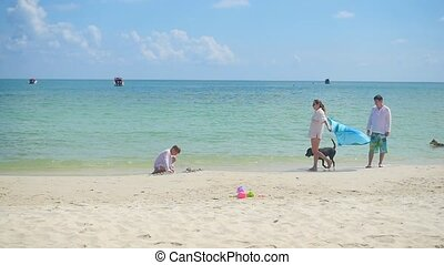 Happy family with child and dog walking on a sandy beach. Tropical island on a hot day