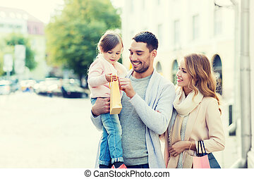 happy family with child and shopping bags in city - sale,...