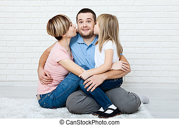 Happy family with child at home. Mother and daughter kissing...