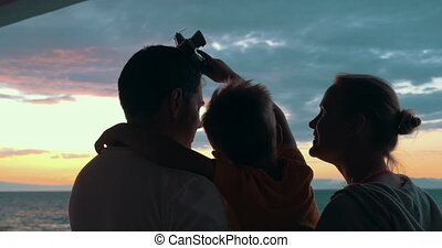 Happy family with child enjoying sunset