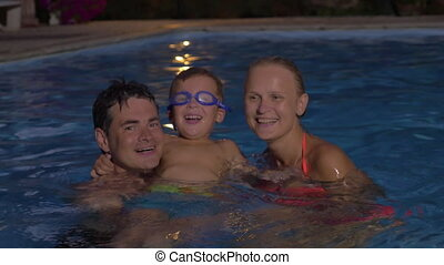 Happy family with child in the pool at night