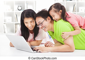 happy family with child looking at laptop