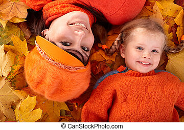 Happy family with child on autumn orange leaf. Outdoor.