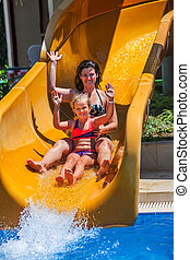Happy family with child on water slide at aquapark