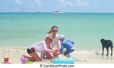 Happy family with children and dog playing on the sandy beach with toys. Tropical island, on a hot day