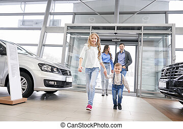 Happy family with children entering dealership showroom.