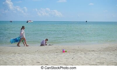 Happy family with children walking on the sandy beach. Tropical island, on a hot day