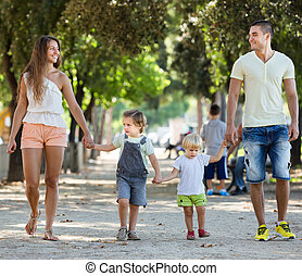 family with childrens playing at park