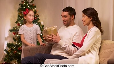 happy family with christmas present at home - holidays,...