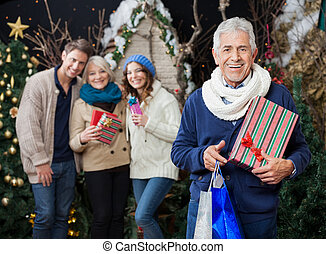 Happy Family With Christmas Presents And Shopping Bags At...