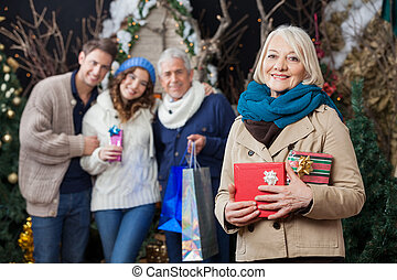 Happy Family With Christmas Presents At Store - Portrait of...