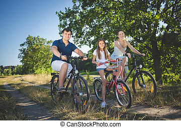 Happy family with cute daughter cycling at meadow