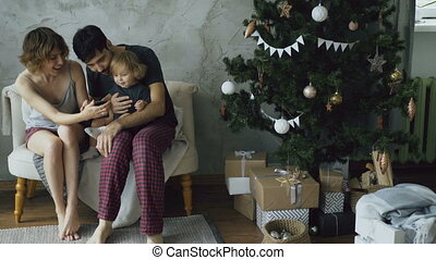 Happy family with cute little daughter sitting near Christmas tree and using smartphone at home