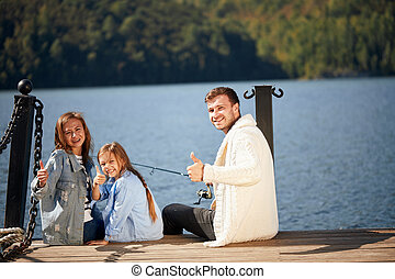 happy family with daughter fishing in pond in fall