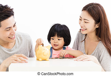 happy family with daughter putting coins into piggy bank