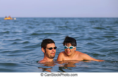 Happy family with father and son playing in the sea
