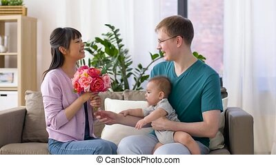 happy family with flowers and baby boy at home