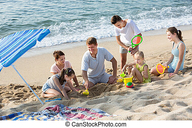 Happy family with four children playing on beach